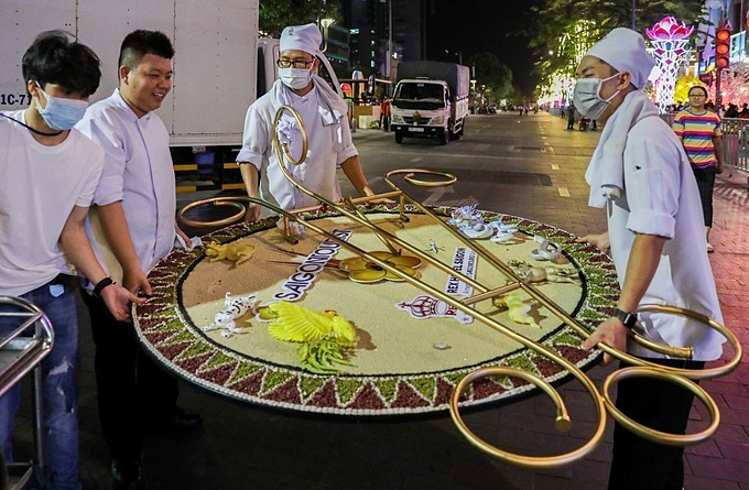 A group of workers move a watch designed with 12 zodiac animals out of the flower street.