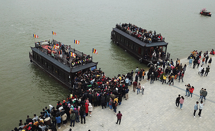 To move from the parking lot to the temple, visitors can travel by boat or electric tourist cars. The wharf is always crowded with people waiting to get on the boat. Tickets for a boat trip cost VND200,000 ($8.8) per person for a round trip. Vietnamese people, especially Buddhist followers have a long tradition of visiting pagodas and temples during Tet to pray for peace and luck for the new year. Vietnam is a predominantly Buddhist nation. It is estimated that over 70 percent of the population are either Buddhist or follow Buddhist practices.