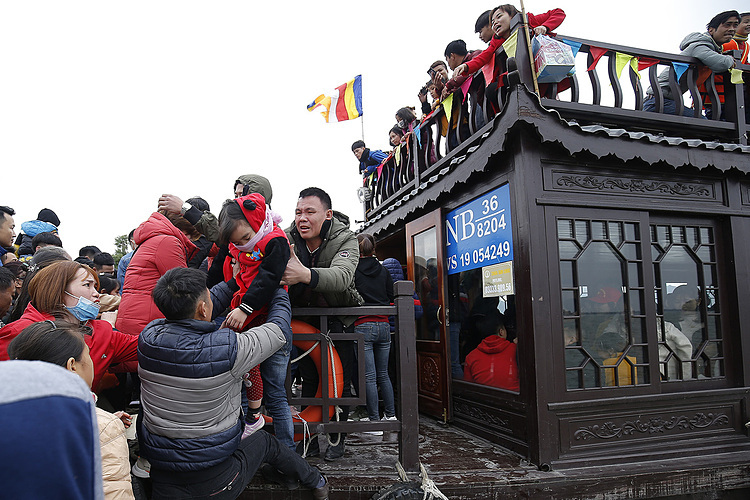 Visitors scramble to board a boat while each boat can only carry a maximum of 60 people.