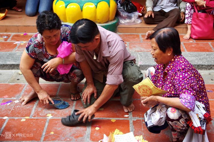 A group of people participate in the villain hitting ritual, an activity that consists of using footwear to repeatedly whack human-shaped paper pieces on the ground. This folk sorcery is also prevalent in Guangdong and Hong Kong and listed as an intangible cultural heritage by the Hong Kong Home Affairs Bureau. The paper figures represent evil energy and the action of crushing them symbolizes protection from bad happenings in real life.I have visited many Chinese Buddhist religious sites, but I have only seen the practice of evil stomping at On Lang Pagoda, said Ngoc Anh, one of the visitors.This practice typically takes place in front of the Tiger altar on Jingzhe Day, translated as the awakening of hibernating insects, which signifies the weather getting warmer. On the Gregorian calendar, this day usually falls on March 5 or 6.