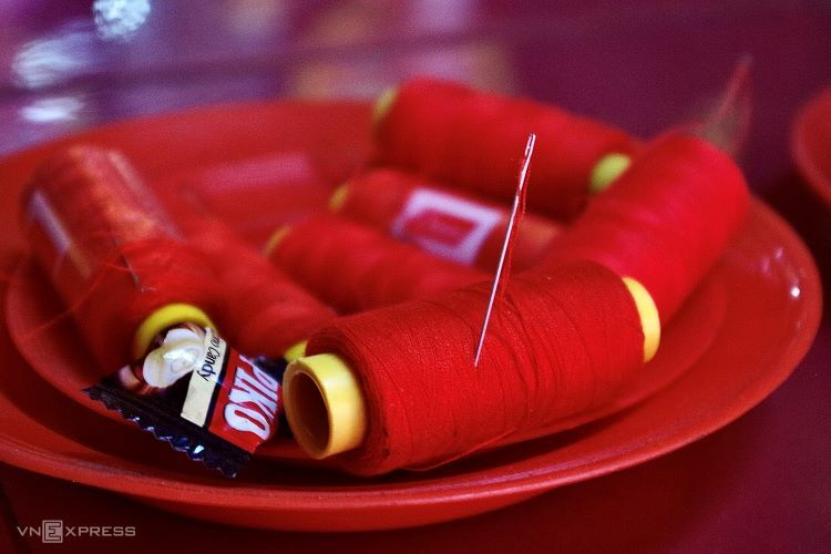 For luck in romance, an additional red thread roll with its needle already threaded is required on top of the typical fruit-bun offerings. Those hoping for a smoother, fulfilling love life place this arrangement at the Hoa Phan phu nhan altar.