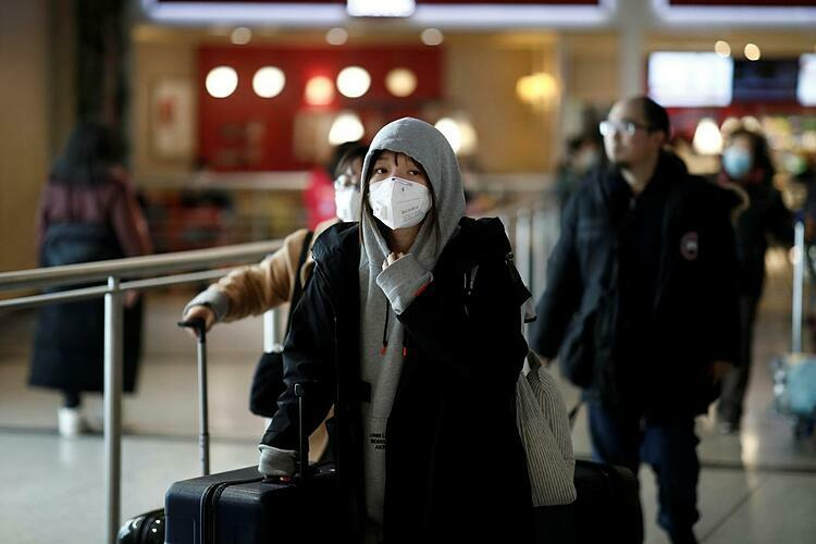 Tourists from an Air China flight from Beijing wear protective masks as they arrive at Charles de Gaulle airport in Paris, France, January 26, 2020. Photo by Reuters/Benoit Tessier.