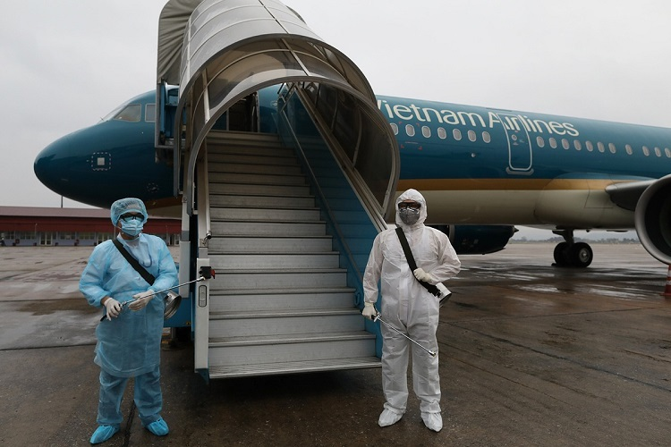 Two personnel from the Hanoi Center for Disease Control, Do Hung Anh and Vu Ba Quang, are in charge of sanitizing the planes, airports and terminals of Noi Bai.