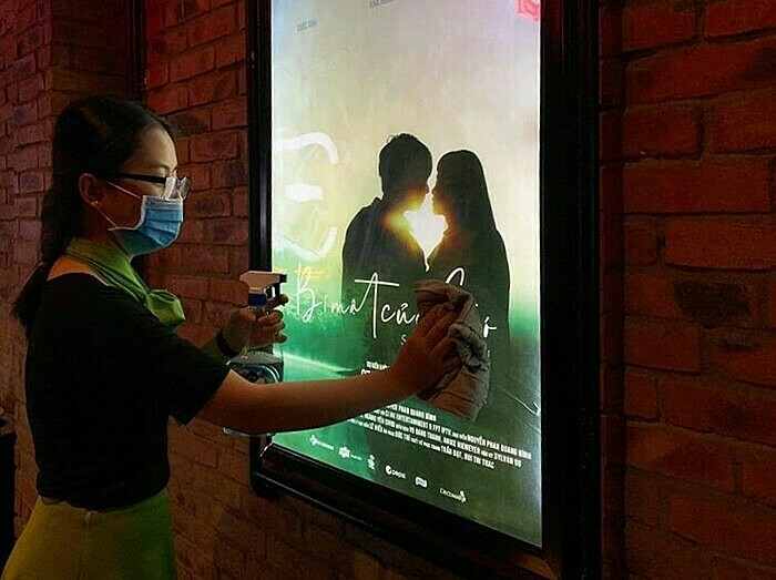 A staff member uses glass cleaner to clean a movie poster at a cinema in ancient town Hue. Photo by Facebook/BHD.