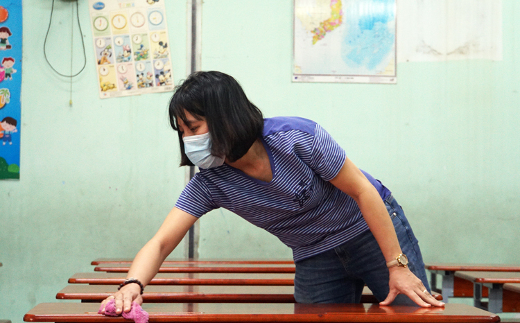 A teacher cleans her classroom in HCMC on February 2. Photo by VnExpress/Manh Tung.
