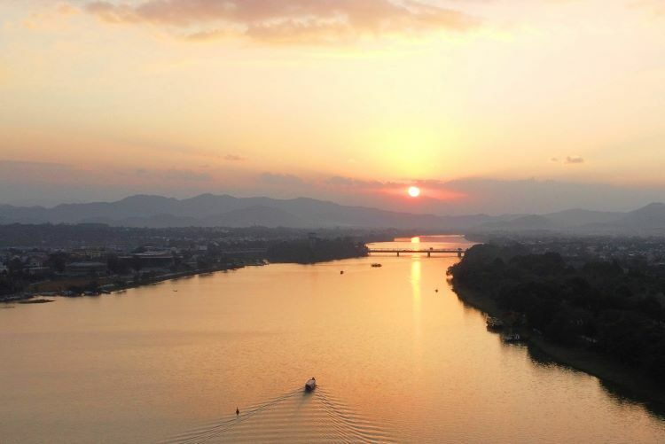 As the sun drops behind the mountains, its beams shine upon the glistening waters of Huong (Perfume) River. Dissecting the ancient town, the river earned its sobriquet from orchard flowers strewn across its waters, adding a floral aroma to its surroundings. The romantic scenery was featured in Vietnam War film Full Metal Jacket.