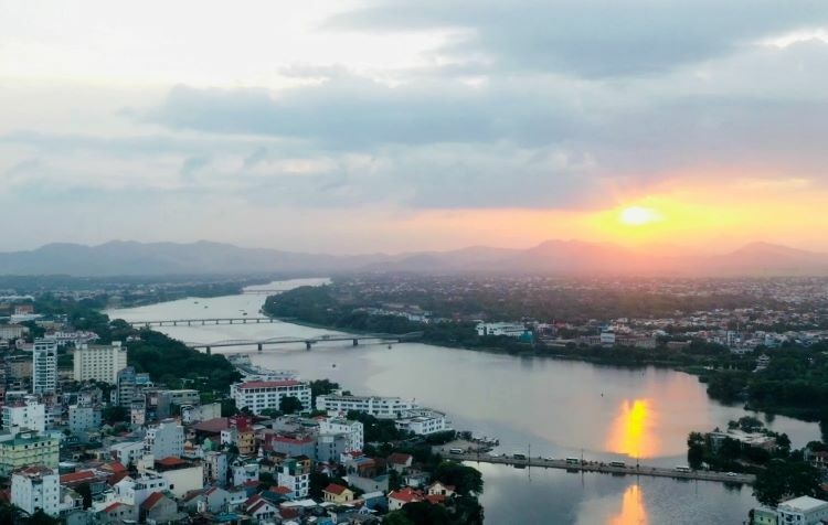 Rays of sunlight radiate from the glossy waters where the Perfume and Nhu Y rivers meet beneath Dap Da Bridge. Iconic Thien Mu Pagoda, alongside French-style buildings like Hue High School for the Gifted line the riverbanks.