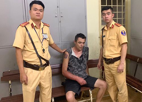 John David Ablett (C) is held at a police station in District 1, HCMC, February 9, 2020. Photo courtesy of HCMC Police.