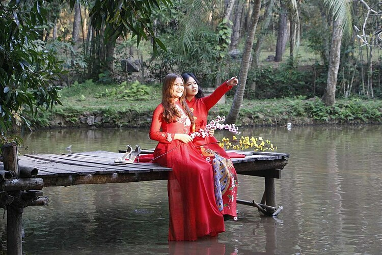 Two girls wearing red ao dai (traditional Vietnamese long dress) pose for a shot inside the pagoda.