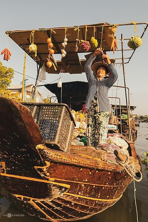 A woman arranges goods on her boat. The market has become a transit point for locals from different provinces that the canals flow through.A wide variety of goods are traded on the waterways, including vegetables, meat, salt and clothes. But fruit is one of the best-selling goods at the Nga Nam market since watermelon, coconut, banana, pineapple and many other fruits are the deltas main produce.