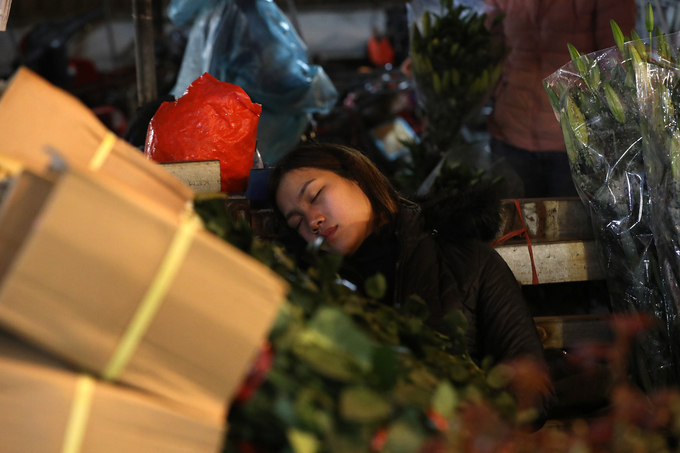 With no customers frequenting her stand, a vendor steals a nap amid her bouquets.
