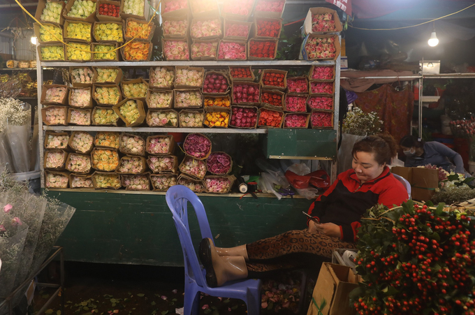 A shop owner watches a video on her phone while waiting for customers to come buy flowers.