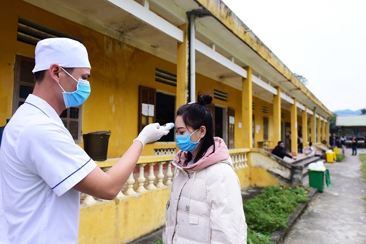 A doctor checks the body temperature of a woman. Everyone gets medically checked twice a day in the morning and in the afternoon. Whoever exhibits symptoms like coughing or fever would be transferred to Lao Cais General Hospital 500 to be monitored.