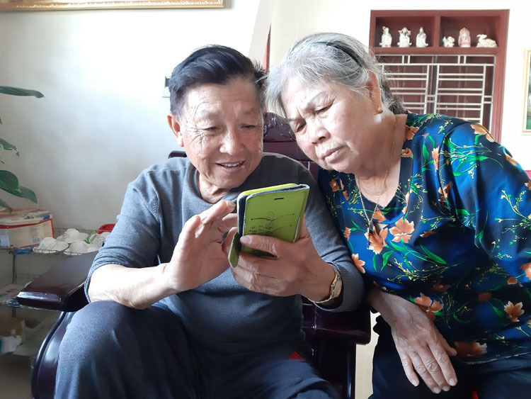 Pham Luong Thuc and his wife using the smartphone their daughter bought last year. Photo by VnExpress/Pham Nga.