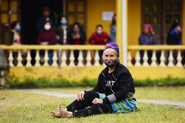 Trang Thi Xua sunbathes on a lawn. Xua, who is of the Mong ethnicity, went to China for work before returning to Vietnam. Her son advised her to go into quarantine for 14 days out of fear of the ongoing epidemic.