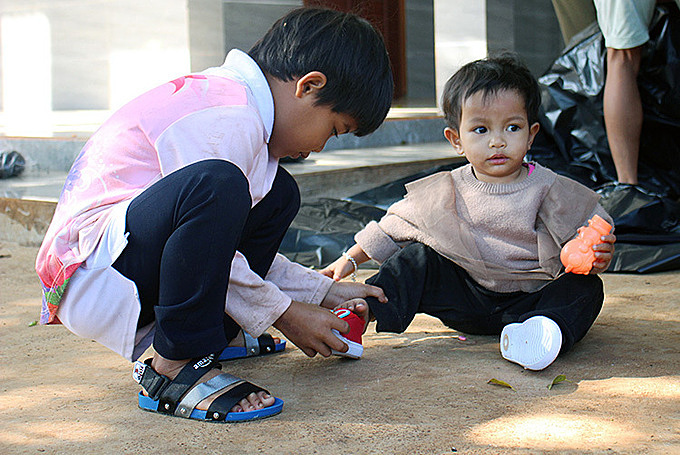 Rahlan H Un (left), 6 and Dinh Thi Thuy Tram, 1. Tram was adopted when she was 4 because he mother passed away and her grandparents could not afford bringing her up. Photo by VnExpress/Phan Diep.