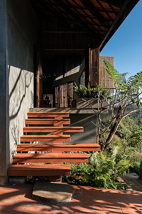 Sharing features of a stilt house, the construction has its ground floor as a storage area. The staircase leading up to the living area is also a favourite place of cats adopted by the young owners.