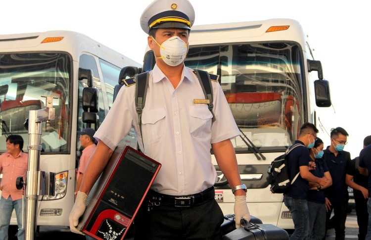 A medical staff brings devices onboard to check passengers body temperature. Photo by VnExpress/Nguyen Khoa.