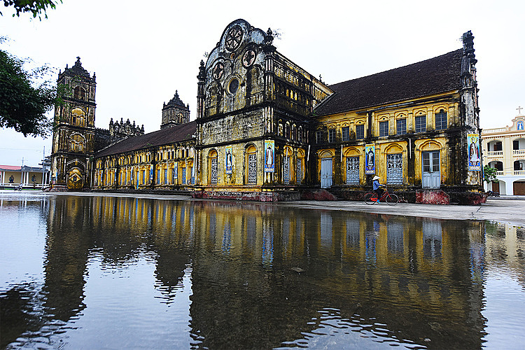 Every time it rains, one part of the yard outside of the cathedral is flooded. Photo by VnExpress/Giang Huy.
