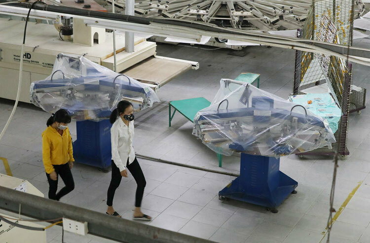 Two workers walk past equipment covered in plastic at South Korean garment company Kumnam Print in Vinh Phuc Province, northern Vietnam, where the coronavirus outbreak has forced it to suspend several production lines, February 2020. Photo by VnExpress/Ngoc Thanh.