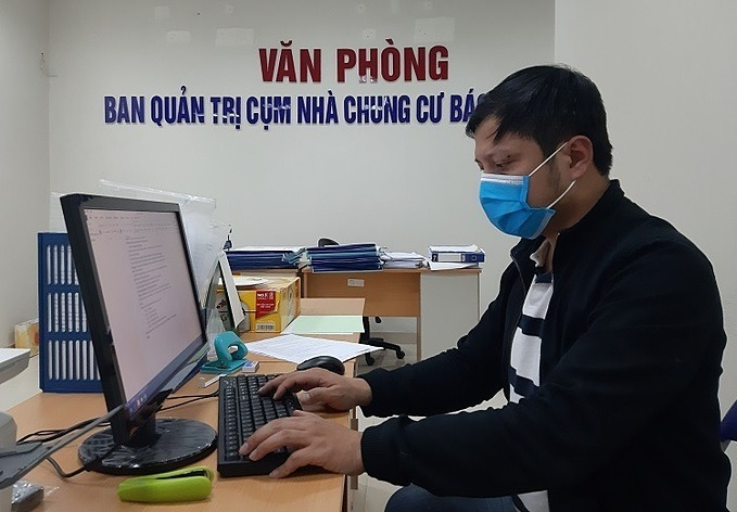 Nguyen Chi Minh wears face mask while working at the apartment buidling in Nam Tu Liem District. Photo by VnExpress/Pham Nga.