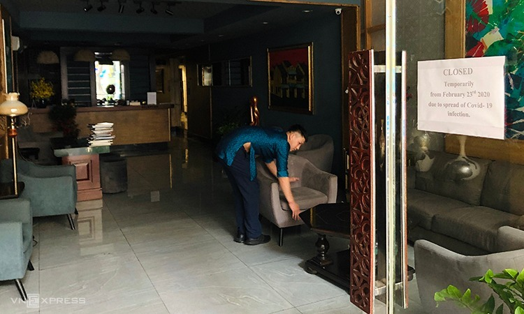 A man rearranges furniture at a closed hotel in Hanoi downtown. Photo by VnExpres/Anh Tu.
