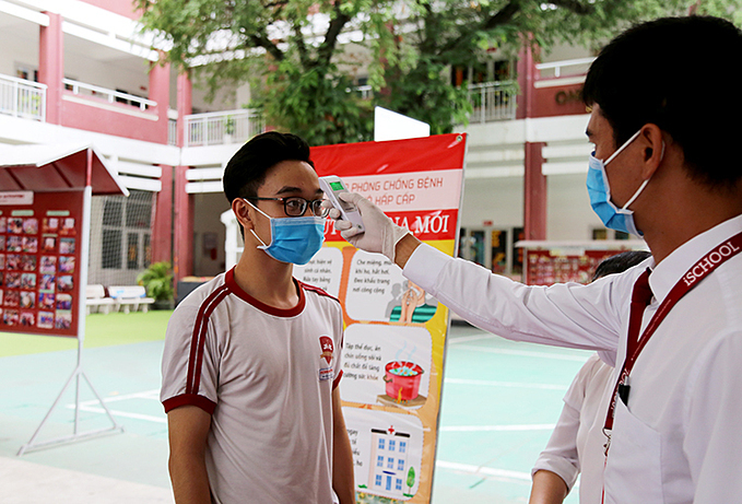 A student of iSchool in Nha Trang has his body temperature checked when he comes back to class on March 2, 2020. Photo by VnExpress/Xuan Ngoc.
