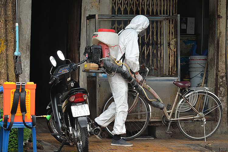 A medical worker on foot disinfected every nook and cranny of nearby streets on March 7, 2020. Photo by VnExpress/Giang Huy.