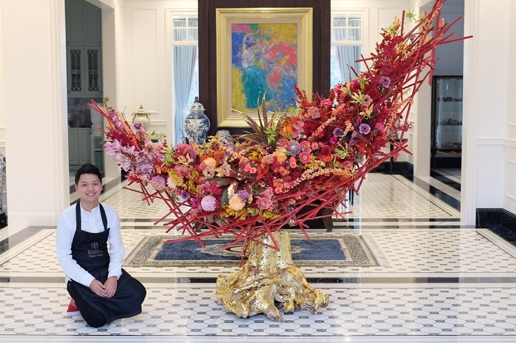 Khoi poses next to his arrangement design Xuan Doan Tu (Spring Reunion) that he created for spring 2020. It took him two weeks to prepare all the materials and one day to complete with the help of four other people. Photo courtersy of Khoi.
