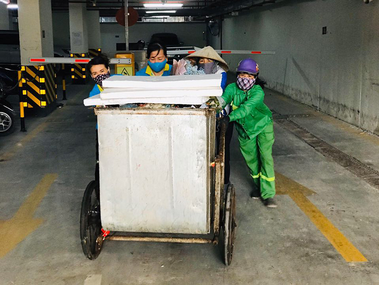 Hanh (L) and her colleagues push the garbage trolley out of an underground garage. Photo by VnExpress/Hai Hien.