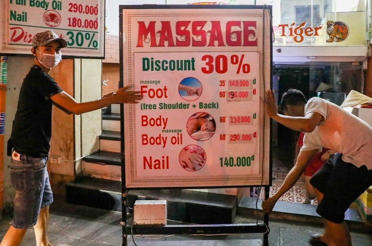 A massage parlor turns off the light and takes its sign boards inside on Saturday evening.
