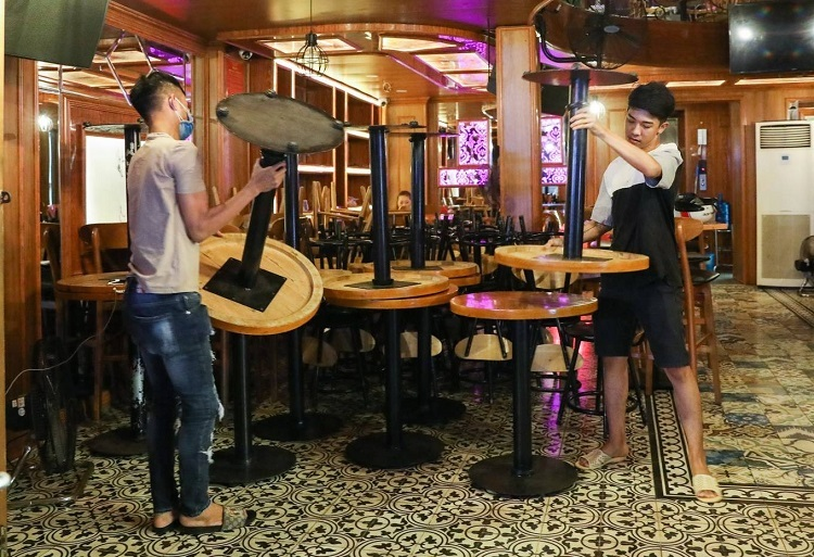 At a beer club, Huy (R), 20, an employee, cleans the tables and puts them in a corner before leaving. He said: Normally, I will work until early morning, but now I will return to my place after this. I will quit working here temporarily to work at a convenience store.