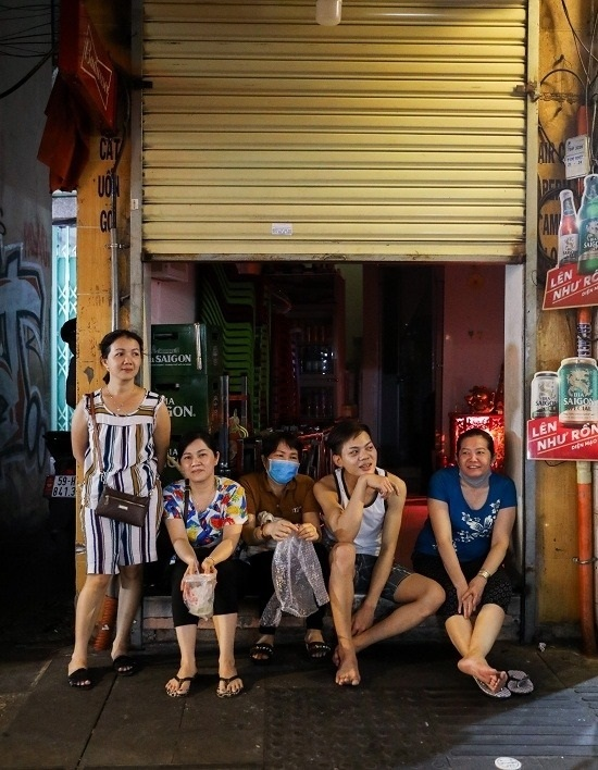 Tran Thi Bach Tuyet (standing) speaks with her staff before closing down her restaurant. This small restaurant costs me VND30 million ($1,293) monthly in rent. If the epidemic is not contained in the next two months, I will return it to the landlord.