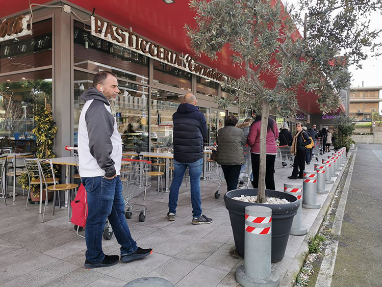 People stand a meter away from each other while waiting outside a supermarket in Italy on March 11, 2020. Photo courtesy of Tran Khanh Huyen.