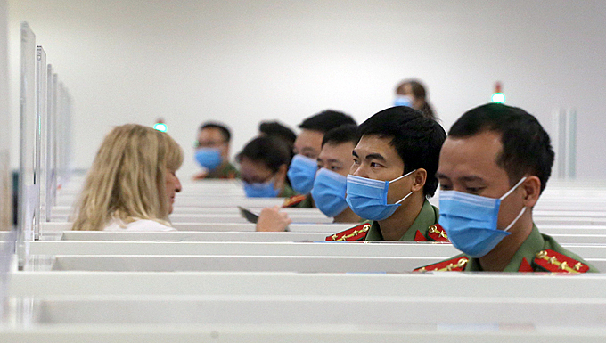 Customs officials at Noi Bai International Airport don masks while at work. Photo by VnExpress/Ba Do.