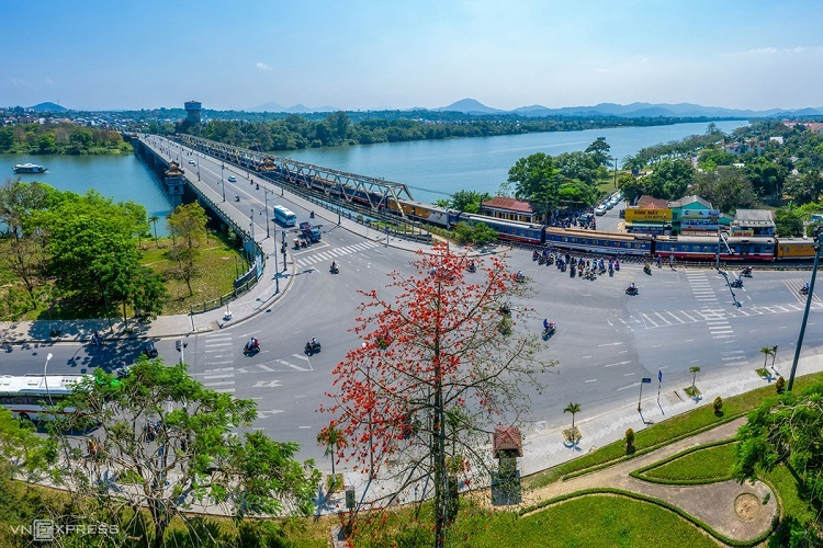 Red cotton trees (cay hoa gao) are in full bloom around the Da Vien Bridge. The trees are tended by workers of Hue Green Park Centre. Red cotton tree flowers typically bloom in March, but due to weather changes they have bloomed earlier this year, Kelvin Long, the photographer who took these shots, explained.