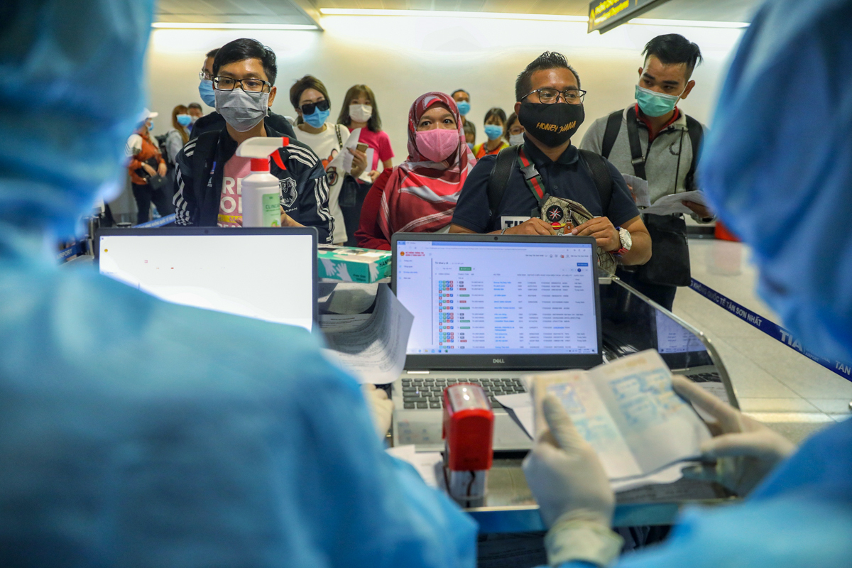 While travelers wore masks, the immigration officers wore head-to-toe protective clothing.