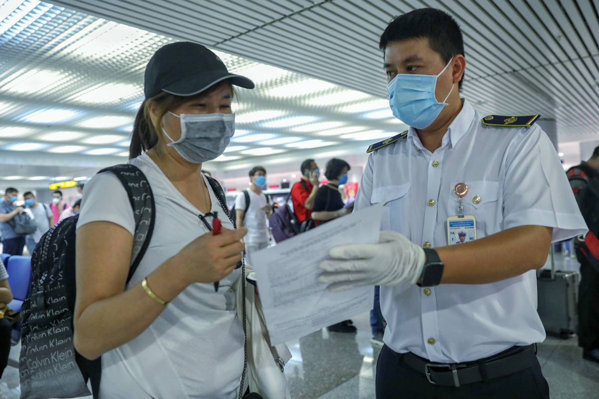 A medical officer (R) guides a Chinese visitor to fill in a form with detailed information about her departure and travel plans.