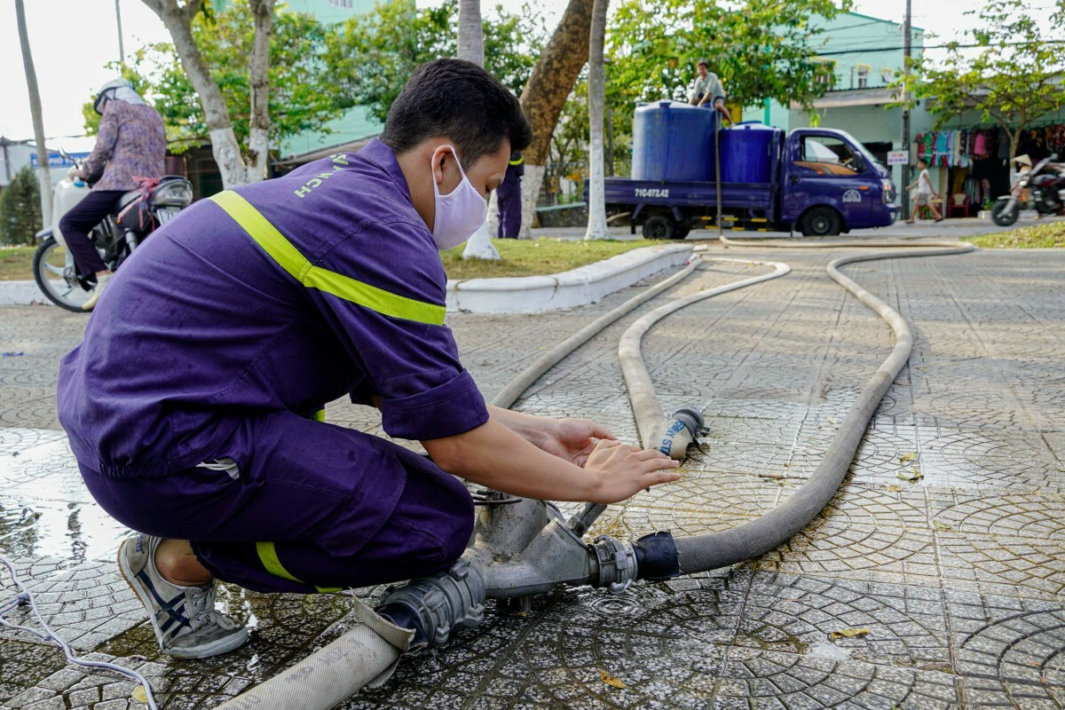 A worker control the valves of pipes that connect with water containers on a truck.
