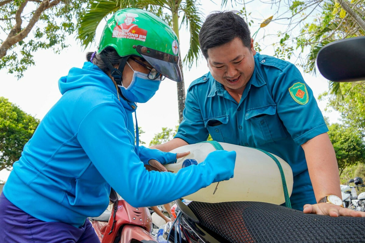 A man helps a woman carry a water can onto a motorbike. A motorbike could carry 1-2 can, each with a capacity of 30 liter. The water could last a day for a family of four if used sparingly.