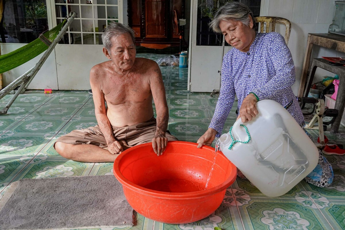 Vinhs wife (R) pours the water into a plastic basin to store it.I ride my wheelchair to collect water every day. Its a little tough, but my grandchild has freshwater to bathe that way, Vinh said.
