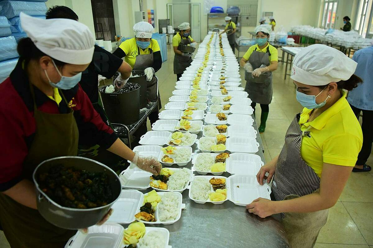 At 4 p.m. on Thursday, a group of 40 people prepare dinner for 776 people who have been quarantined at Son Tay Military School in Hanoi. Meal boxes fill the 300-square-meter cafeteria.  Between March 13 and 15, the camp received 776 people. Except for eight foreigners, the remainder are Vietnamese who returned from Europe. Prior to this batch, the camp received 752 people returning from South Korea who completed their 14-day period starting February 25.