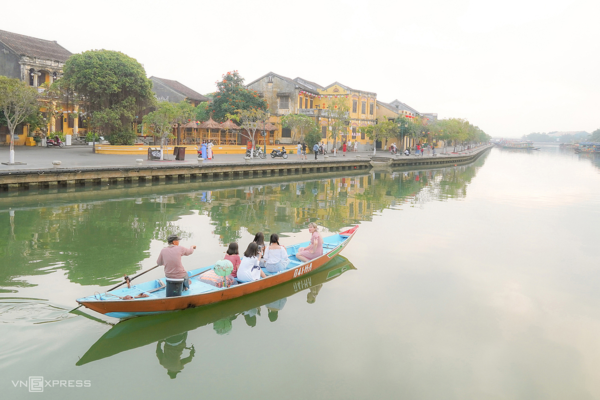 Boats carrying tourists to visit on the Hoai River in the early morning sun, when the atmosphere is still slightly dew.  Sitting on a small boat smoothly passing through the streets and craft villages on the banks of the river will be an interesting experience for tourists, photographer Do Anh Vu (living in Hoi An), the author of the photo series, said.