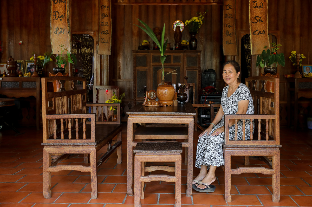 Giac sitting in the living area of her house, which is used to receive guests and gather the family. The house looks inviting with a table set, Buddhist altar and scrolls with couplets. In 2017 Giac's family hired over 30 workers and artisans to build the homestay. It took two years.The 67-year-old says: Coconut trees were a big part of my childhood and so I'd always wanted a house that embodied them. Given our extensive land, green garden and proximity to the river, my children and grandchildren encouraged me to open a homestay right on the property.