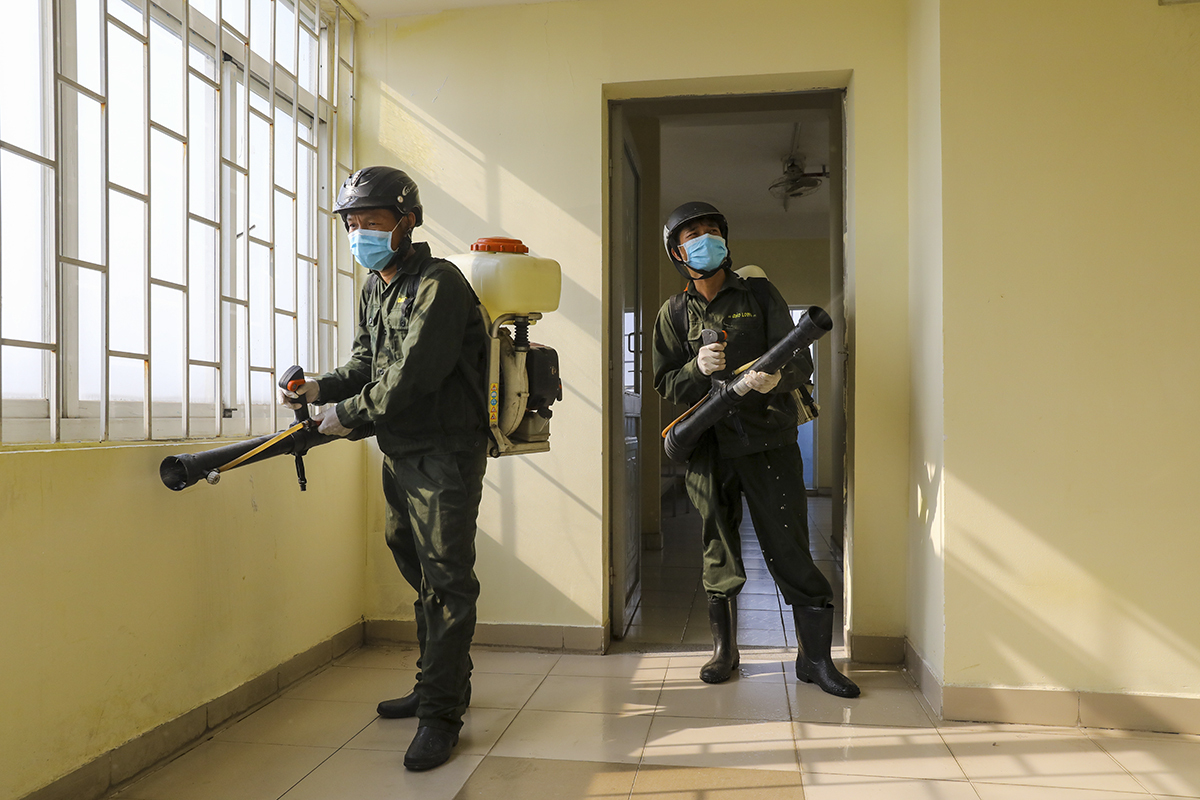 Staff spray disinfectant at a dormitory in Ho Chi Minh City for the city to use it as centralized facility to quarantine those coming to Vietnam from areas hit by the Covid-19, March 18, 2020. Photo by VnExpress/Quynh Tran