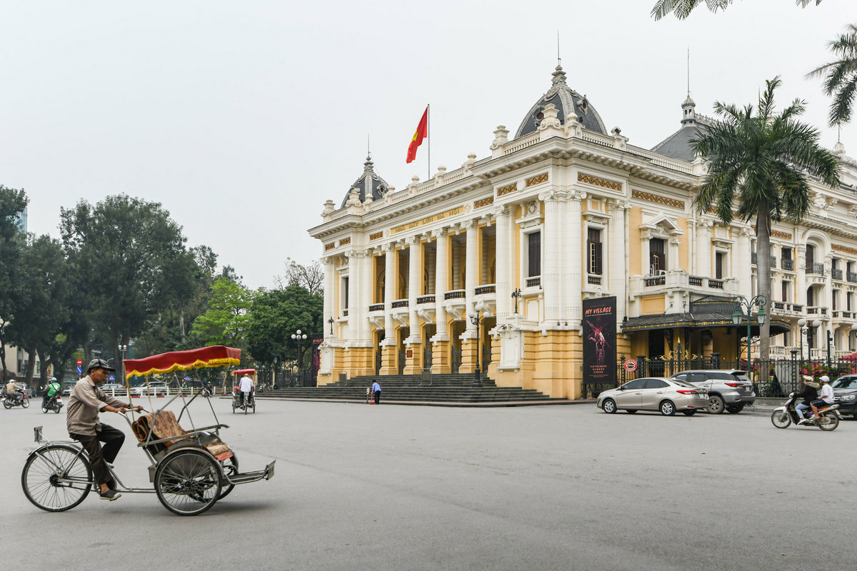 The cyclos without passengers rushing across Hanoi Opera House. This area is usually crowded on normal days as visitors often come here to take photos. But now there are very few people here.