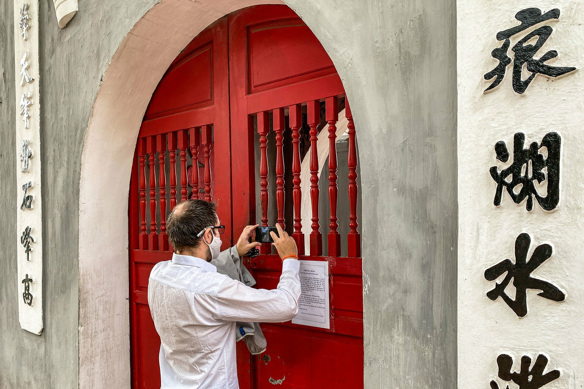 Ion Nicolae Rosescu, a Romanian tourist tries to take a picture of The Huc Bridge through the locked door of Ngoc Son Temple on Hoan Kiem Lake. The temple was closed on March 14. Ion said during his two-week trip from Ho Chi Minh City to Hue, Quang Ninh and Hanoi, all attractions were shut down. All he could do at the moment is walking around the streets and eating fast food while waiting for his flight back to Romania tonight.I had to change my flight because the airlines was temporarily stopped working due to the pandemic, Rosescu said.