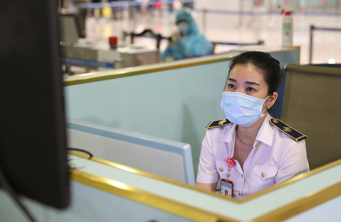 Ngoc keeps a watchful eye on the body temperature scanner