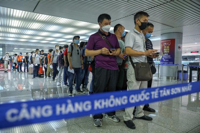 Long queues of passengers wearing masks at Tan Son Nhat International airport on March 17. Photo by VnExpress/Huu Khoa