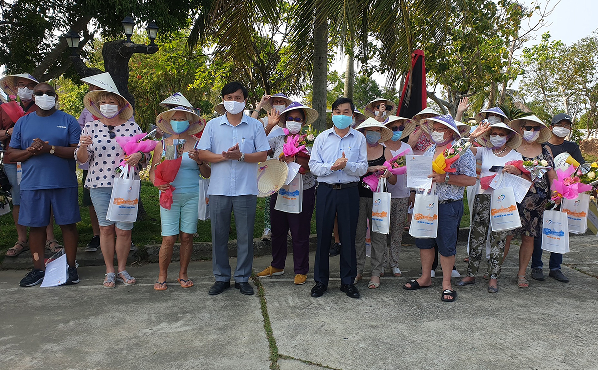 Foreign tourists pose with Thua Thien-Hue officials as they hold souvenirs and quarantine completion certificates, March 24, 2020. Photo by VnExpress/Vo Thanh.